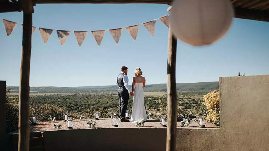 A-happy-couple-share-a-tender-moment-while-overlooking-the-Shamwari-grounds